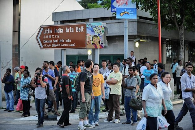 Bystanders gather on the corner of a street in Little India, following a riot the day before by South Asian workers, in the worst outbreak of violence in more than 40 years in the tightly controlled city-state, on December 9, 2013