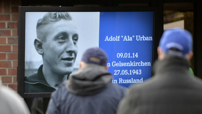 A Schalke supporters look  at a picture of Adolf Urban, a storied player for  German soccer club FC Schalke 04 who was killed in Eastern Front fighting in World War II and  and who is being reburied in a cemetery in Gelsenkirchen, Germany, Wednesday, Nov. 20, 2013. Urban helped Schalke win five German championships and one German cup before he died 1943  in Russia. His body returned home after 70 years now to a cemetery overlooking the Schalke stadium