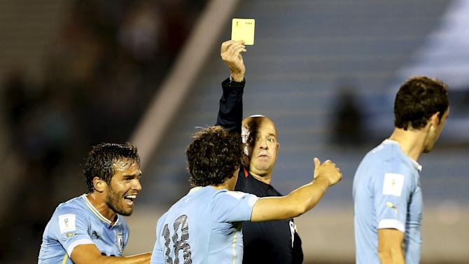 Uruguay's Corrijo receives a yellow card from referee Lopes during their 2018 World Cup qualifying soccer match against Colombia in Montevideo