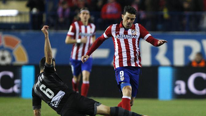 Atletico's David Villa, right, competes with Loukas Vyntra from Greece, left, during a Spanish La Liga soccer match between Atletico de Madrid and Levante at the Vicente Calderon stadium in Madrid, Spain, Saturday, Dec. 21, 2013