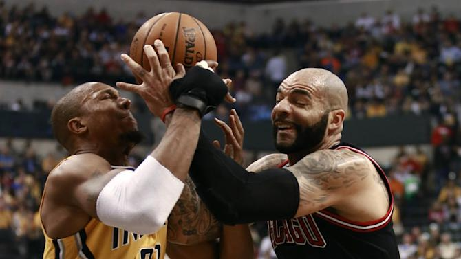 Chicago Bulls forward Carlos Booozer, right, competes with Indiana Pacers forward David West for the basketball in the first half of an NBA basketball game in Indianapolis, Friday, March 21, 2014