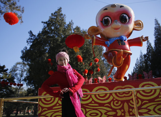 A woman poses in front of a monkey-shaped installation in Beijing, China, Feb. 5, 2016. (Reuters)