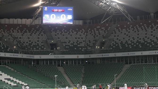 Legia Warszawa and Apollon Limassol FC players vie for the ball during their Group J Europa League soccer game at the empty Pepsi Arena stadium in Warsaw, Poland, Thursday, Oct. 3, 2013. UEFA ordered Legia to play the match behind closed doors because of  improper conduct of supporters during recent Champions League games. Legia was also fined 150,000 euros