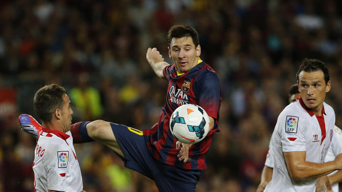 FC Barcelona's Lionel Messi from Argentina, in action with Sevilla's Fernando Navarro, left, and Piotr Trochowski from Poland, right, during a Spanish La Liga soccer match at the Camp Nou stadium in Barcelona, Spain, Saturday, Sept. 14, 2013