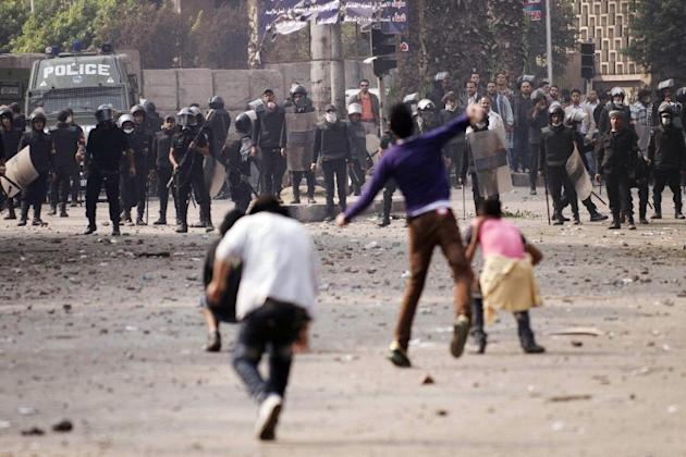 Egyptians youth and demonstrators hurl stones towards Egyptian security forces on November 27, 2012.