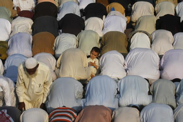 A boy stands amid supporters of Jamaat-e-Islami and the Pakistan Tehreek-e-Insaf political party, as they perform evening prayers during a protest in Karachi
