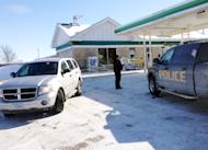Authorities gather at a gas station in West Branch, Iowa, where a missing newborn was found alive Friday, Feb. 7, 2014. Police said they found Kayden Powell, who's nearly a week old, after they heard the newborn crying and found the child in a gray plastic storage bin outside the gas station. Police said the baby was in excellent health. (AP Photo/Ryan J. Foley)