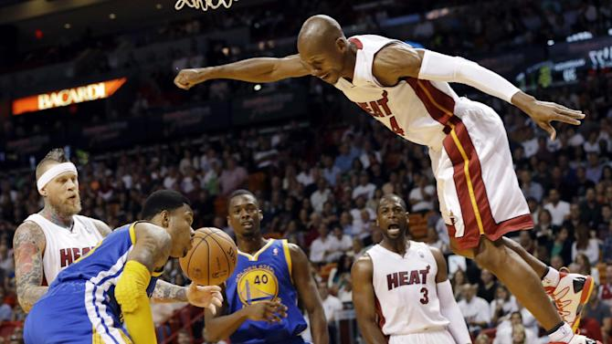 Miami Heat's Ray Allen, right, is fouled after shooting a basket during the first half of an NBA basketball game against the Golden State Warriors, Thursday, Jan. 2, 2014, in Miami. Also shown are Golden State Warriors' Kent Bazemore, left, and Harrison Barnes (40) and Heat's Dwyane Wade (3)
