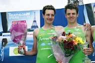 Britain's Alistair Brownlee (L) and his brother Jonathan pose on the podium after finishing first and second, respectively, at the Paris triathlon in July 2011. The two will be looking over their shoulders in Tuesday's triathlon after the women's event continued a rich tradition of Olympic surprises
