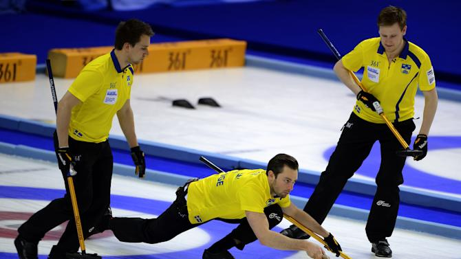 Sweden's skip Sebastian Kraupp (C) delivers a stone during his play against Norway in their bronze medal game at the World Men's Curling Championship on April 8, 2012 in Basel. AFP PHOTO / FABRICE COFFRINI (Photo credit should read FABRICE COFFRINI/AFP/Getty Images)
