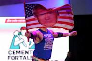 U.S. wrestler Sam Adonis, 27, role-playing as a fan of U.S. President Donald Trump, waves a flag with Trump's face during a wrestling fight at the Coliseo Arena, in Mexico City, Mexico, February 12, 2017. REUTERS/Edgard Garrido