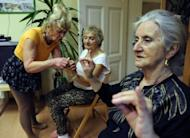 """Ludwika Kochman (left) a volunteer of the """"Little Brothers of the Poor"""" association which supports seniors citizens, leads a gym session in Poznan, Poland on March 5"""