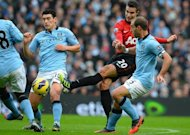 Manchester City midfielder Gareth Barry (L) and defender Pablo Zabaleta (R) try to block a shot from Manchester United striker Robin Van Persie during the Premier League match at the Etihad Stadium in Manchester, north-west England, on December 9, 2012. Barry has been charged over his behaviour during his side's 3-2 loss to United, the Football Association announced Tuesday