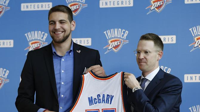 Oklahoma City Thunder forward Mitch McGary, left, and Thunder Executive Vice President and General Manager Sam Presti, right, hold a basketball jersey as McGary is introduced during a news conference in Oklahoma City, Friday, June 27, 2014