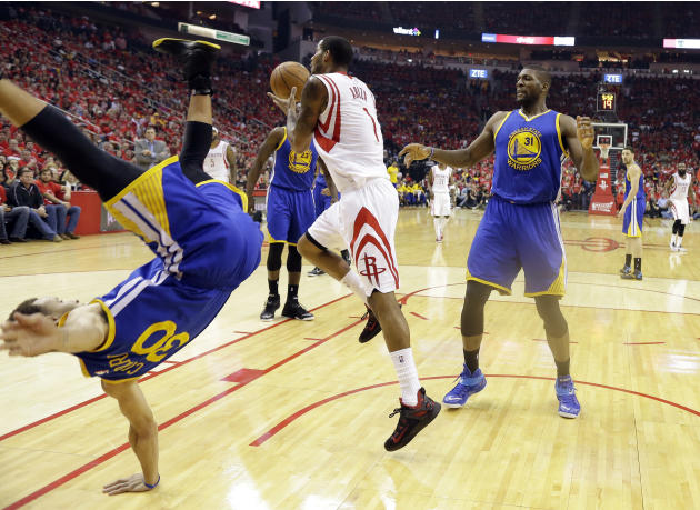 Golden State Warriors guard Stephen Curry (30) topples over Houston Rockets forward Trevor Ariza (1) during the first half in Game 4 of the Western Conference finals of the NBA basketball playoffs as