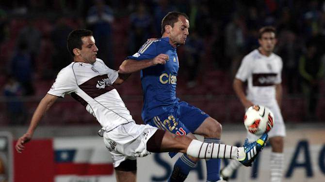 Chile's Universidad de Chile's Gustavo Lorenzetti, right, and Argentina's Lanus Jorge Ortiz go for the ball during a Copa Sudamericana soccer match in Santiago, Chile, Wednesday, Sept. 25, 2013