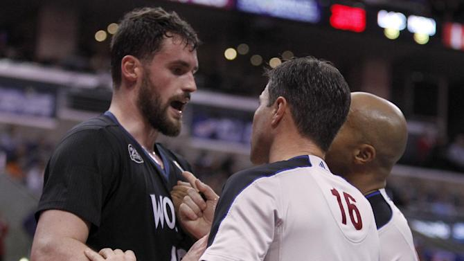 Referees David Guthrie (16) and Marc Davis, right, try to calm down Minnesota Timberwolves forward Kevin Love, left, after a physical foul by Los Angeles Clippers forward Matt Barnes in the second half of an NBA basketball game in Los Angeles on Sunday, Dec. 22, 2013. Clippers forward Matt Barnes was ejected from the game for physical play, but the Clippers won the game 120-116 in overtime