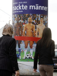"In this picture taken Oct. 18, 2012 two people walk past a poster showing three naked men which has had red tape added to cover the sensitive parts of the three men, in Vienna, Austria. Poster reads: ""Naked Men"". A prestigious Vienna museum, The Leopold Museum, has been forced to cover up a graphic poster advertising a new show devoted to male nudity, after protests that it is offensive. The show — ""Nude Men from 1800 to Today"" — opened its doors Friday Oct. 20, looking at how artists have dealt with the theme of male nudity over the centuries. (AP Photo/Ronald Zak)"