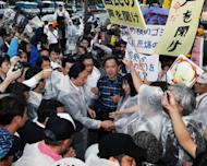 Former Japanese Prime Minister Yukio Hatoyama (centre) shakes hands with anti nuclear activists at an anti nuclear power plant rally in front of the Japanese Prime Minister's official residence in Tokyo on Friday