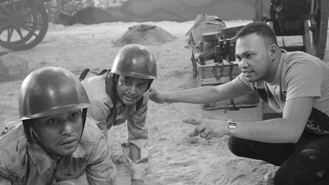 """In this undated photo released by Forward Entertainment, Filipino director Borinaga Alix Jr., right, instructs actors on the set of his film """"Death March"""" inside a studio in suburban Marikina, east of Manila, Philippines. Alix chose to film """"Death March"""" in black-and-white and almost entirely inside a studio using hand-painted backdrops, with close-ups of actors' painted faces portraying their struggles with nightmares and hallucinations in one of the bloodiest episodes of World War II. (AP Photo/Forward Entertainment) NO SALES"""