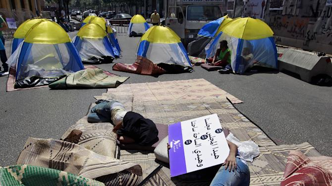 "Protesters stage a sit-in on a street near the parliament building in Beirut, Lebanon, Friday, June 21, 2013. A group of protesters stayed overnight to protest against the 128-member parliament that extended its term by a year and a half last month, skipping scheduled elections because of deteriorating security conditions in the country related to the war in Syria. The Arabic on the placard reads, ""This council (parliament) is council, and the square is ours."" (AP Photo/Bilal Hussein)"