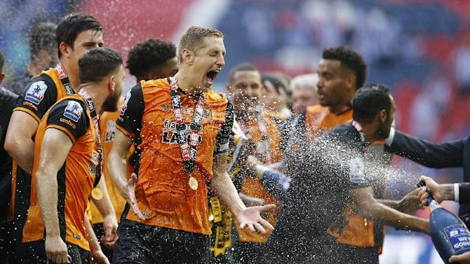 Hull City's Michael Dawson is sprayed with champagne as they celebrate winning promotion back to the Premier League