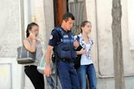 A policeman escorts two students from a private school near a bank where four people were taken hostage in the southern French city Toulouse