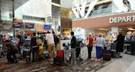 This file photo shows passengers queuing at a check-in counter in Singapore's Changi International Airport, in 2011. Singapore police warned on Tuesday that members of a Chinese crime syndicate were believed to be stealing money from the bags of passengers while they slept on flights to and from the country