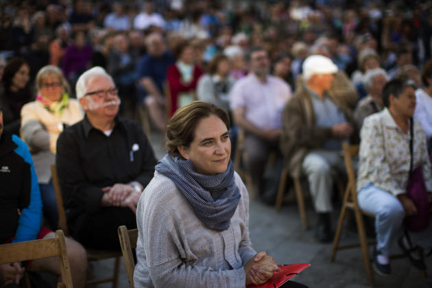 The leader of leftist coalition Barcelona Together, Ada Colau, waits her turn to give a speech during a campaign meeting in Barcelona, Spain, Friday, May 22, 2015. Spain could be set for a political u