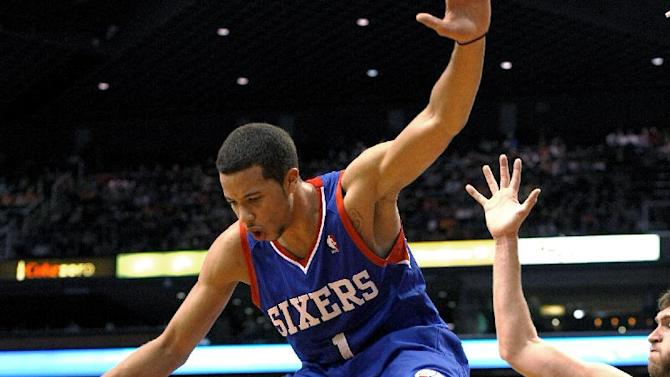 Philadelphia 76ers guard Michael Carter-Williams (1) fouls Phoenix Suns forward Channing Frye (8) during the third quarter of an NBA basketball game Saturday, Dec. 28, 2013, in Phoenix