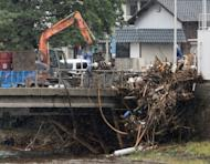 Workers remove debris from the railing of a bridge in Kumamoto prefecture, on Japan's southern island of Kyushu on July 13. Rainfall of up to 81.7 centimetres has been recorded in hardest-hit Aso, situated at the foot of a volcano, where at least 18 people were killed and four others were still missing