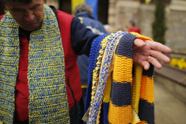 Adams offers blue and yellow scarves from the Marathon Scarf Project to 2014 Boston Marathon athletes at Old South Church near the race's finish line in Boston