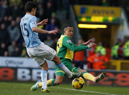 Manchester City's Navas challenges Norwich City's Olsson during their English Premier League soccer match at Carrow Road in Norwich, eastern England