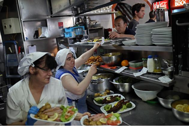 Kitchen staffers and waiters in a Portuguese traditional food restaurant work, during a busy lunch time, in Lisbon, Friday, May 22, 2015. European Central Bank head Mario Draghi said tough measures to