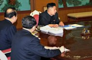 "This photo, released by North Korea's official Korean Central News Agency (KCNA) on January 27, 2013, shows N.Korean leader Kim Jong-Un (R) attending a consultative meeting with the government officials at an undisclosed location in N.Korea. During the meeting, Kim ordered ""substantial and high-profile important state measures,"" fuelling speculation of an imminent nuclear test"