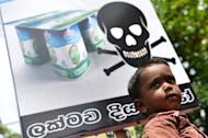 A Sri Lankan child looks on as pro-government activists protest the alleged contamination of milk powder outside the factory of dairy giant Fonterra in a Colombo suburb on August 22, 2013. A Sri Lankan court on Friday lifted a ban on the sale of milk products of New Zealand dairy giant Fonterra which has been under pressure over a global botulism scare