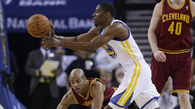 Golden State Warriors guard Jordan Crawford, right, passes next Cleveland Cavaliers guard Jarrett Jack, center, during the first half of an NBA basketball game on Friday, March 14, 2014, in Oakland, Calif