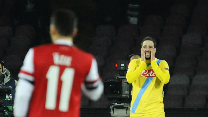 Napoli's Gonzalo Higuain, right, walks off the pitch at the end of a Champions League, group F, soccer match between Napoli and Arsenal, at the Naples San Paolo stadium, Italy, Wednesday, Dec. 11, 2013. Ten-man Arsenal advanced to the Champions League knockout phase for the 14th consecutive year despite a 2-0 loss Wednesday at Napoli, which was eliminated. Gonzalo Higuain scored in the 73rd minute but the San Paolo stadium was soon silenced when word arrived that Borussia Dortmund had scored a late goal in a 2-1 win at Marseille to win Group F