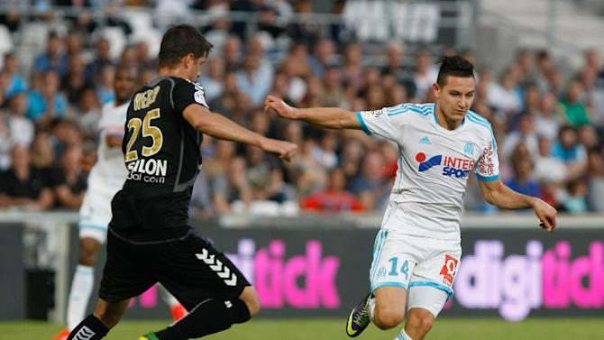 Marseille's midfielder Florian Thauvin, right, dribbles past Stade de Reims' defender Anthony Weber, to score against Reims, during their League One soccer match, at the Velodrome Stadium, in Marseille, southern France, Saturday, Oct. 26, 2013