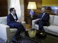 Greece's Prime Minister Alexis Tsipras, left, speaks with EU Finance Commissioner Pierre Moscovici during their meeting at Maximos Mansion in Athens, Wednesday, Feb. 15, 2017. The European Union's financial affairs chief is in Greece for talks on the bailout-dependent country's slow-moving negotiations with its international creditors. (AP Photo/Thanassis Stavrakis)