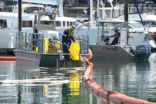 A cleanup crew member works aboard a boat on the scene of what is believed to be a diesel fuel spill in Vancouver's False Creek, Monday June 15, 2015. Hundreds of metres of containment boom have been set up in the area. THE CANADIAN PRESS/Jonathan Hayward