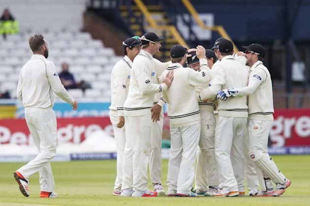 New Zealand's Tom Latham, centre of group and wearing a helmet, is congratulated by teammates after catching England's Joe Root off the bowling of Mark Craig, left, on the fifth day of the sec
