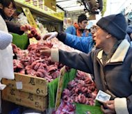File photo of an elderly shopper buying octopus from a fish dealer in the Ameyoko shopping district in Tokyo. Household spending fell more sharply than expected in January with the nation still stuck in its deflationary rut, government data showed Friday