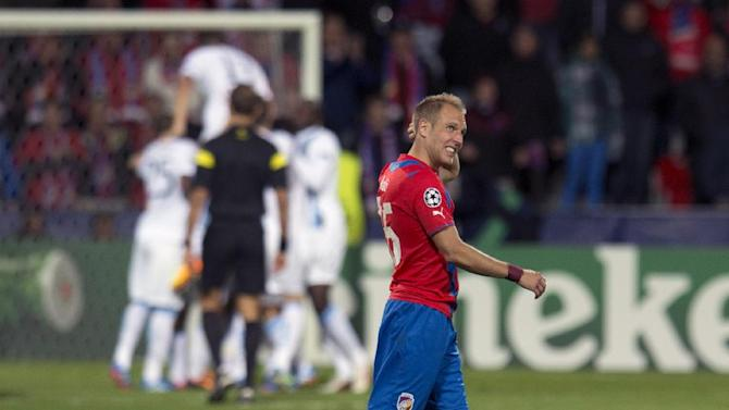 Viktoria Plzen's midfielder Daniel Kolar walks acroos the pitch  as Manchester City's players, rear, celebrate a goal during the Champion's League Group D soccer match against Viktoria Plzen in Plzen, Czech Republic, Tuesday, Sept. 17, 2013. (AP Photo, CTK/Michal Kamaryt)