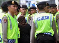 """An Indonesian woman walks past Indonesian policemen in Jakarta on February 20, 2012. An Indonesian woman drowned her nine-year-old son in the bath, claiming she was worried that his """"small penis"""" would affect his prospects for the future, a police spokesman said Thursday"""