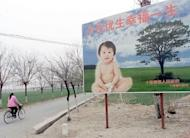 A woman cycles past a billboard encouraging couples to have only one child in a suburb of Beijing. The husband of a Chinese woman whose forced abortion seven months into her pregnancy caused an uproar has disappeared and her family is enduring daily harassment, a relative said Tuesday