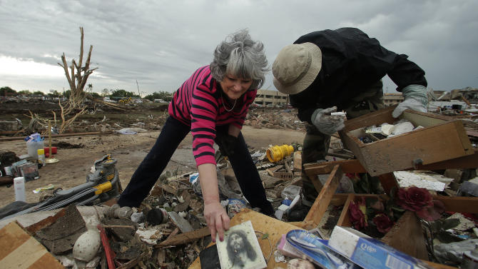 Lea Bessinger salvages a picture of Jesus as she and her son Josh Bessinger sort through the rubble of the elder Bessinger's tornado-ravaged home Tuesday, May 21, 2013, in Moore, Okla. A huge tornado roared through the Oklahoma City suburb Monday, flattening an entire neighborhoods and destroying an elementary school with a direct blow as children and teachers huddled against winds. (AP Photo/Charlie Riedel)