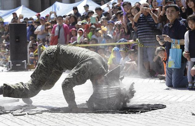 People watch a soldier from the South Korean army special forces break stone plates with his head during a martial arts demonstration for Children's Day at the War Museum in Seoul, Tuesday, May 5,