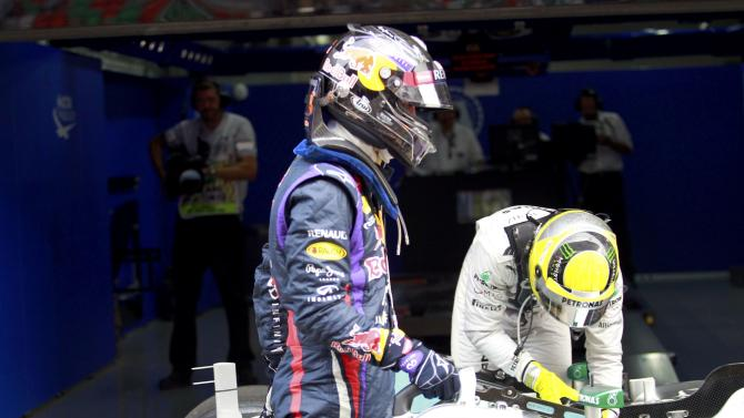 Red Bull Formula One driver Vettel carries a fan to his car after parking at the completion of the qualifying session of the Indian F1 Grand Prix at the Buddh International Circuit in Greater Noida
