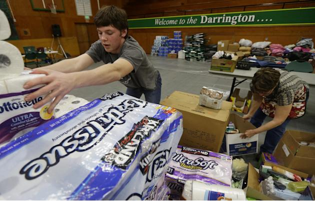 Volunteers, including Oliver Rankin, left, the son of Darrington Mayor Dan Rankin, and Laura Grimmer, right, sort items, Wednesday, March 26, 2014 that were donated to help families affected by the ma